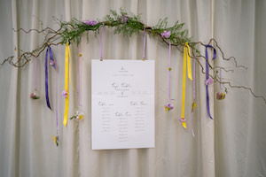 Whimsical hanging table plan with purple and yellow ribbon